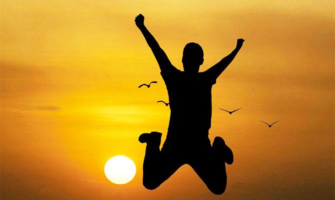 夕焼けに向かってジャンプする男性