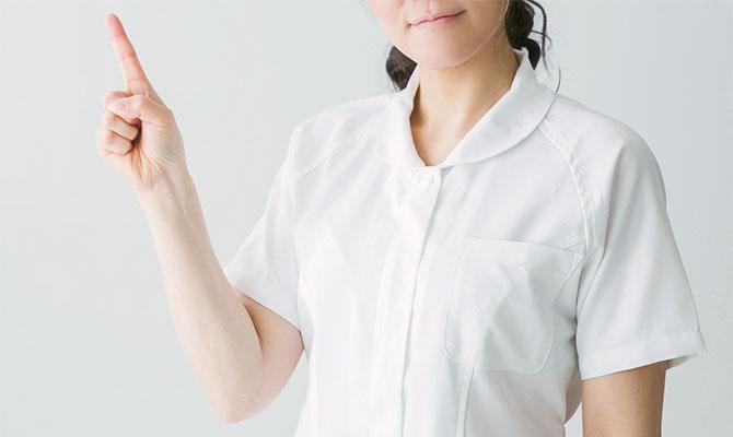 人差し指を立てる白衣の女性